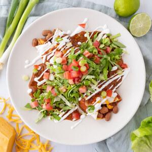Smothered Cheesy Bean Burrito with Enchilada Sauce & Lime Crema